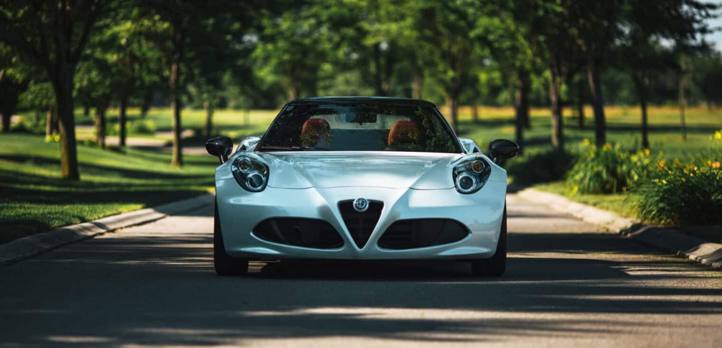 Display The 2020 Alfa Romeo 4C Spider parked on a tree-lined road.