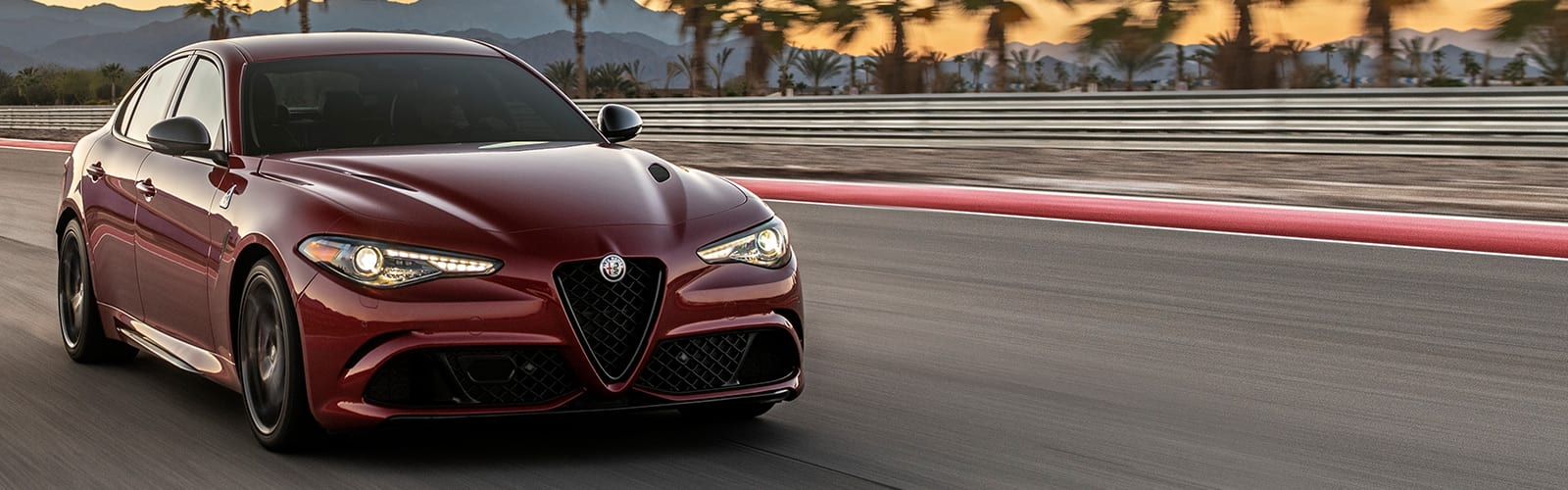 A 2020 Alfa Romeo Giulia Quadrifoglio being driven on a track at sunset.