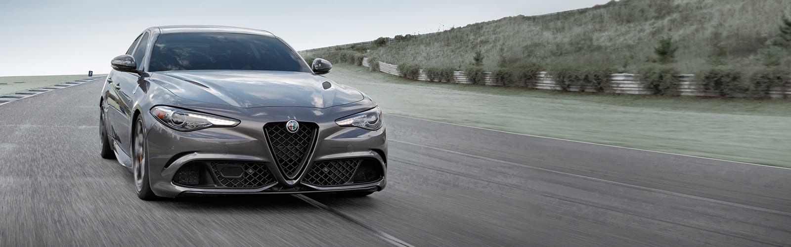 A front end view of a gray 2020 Alfa Romeo Giulia Quadrifoglio being driven on a track.