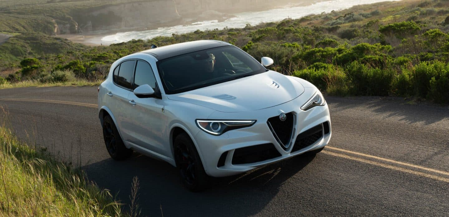 Display The 2020 Alfa Romeo Stelvio Quadrifoglio on a winding country road.
