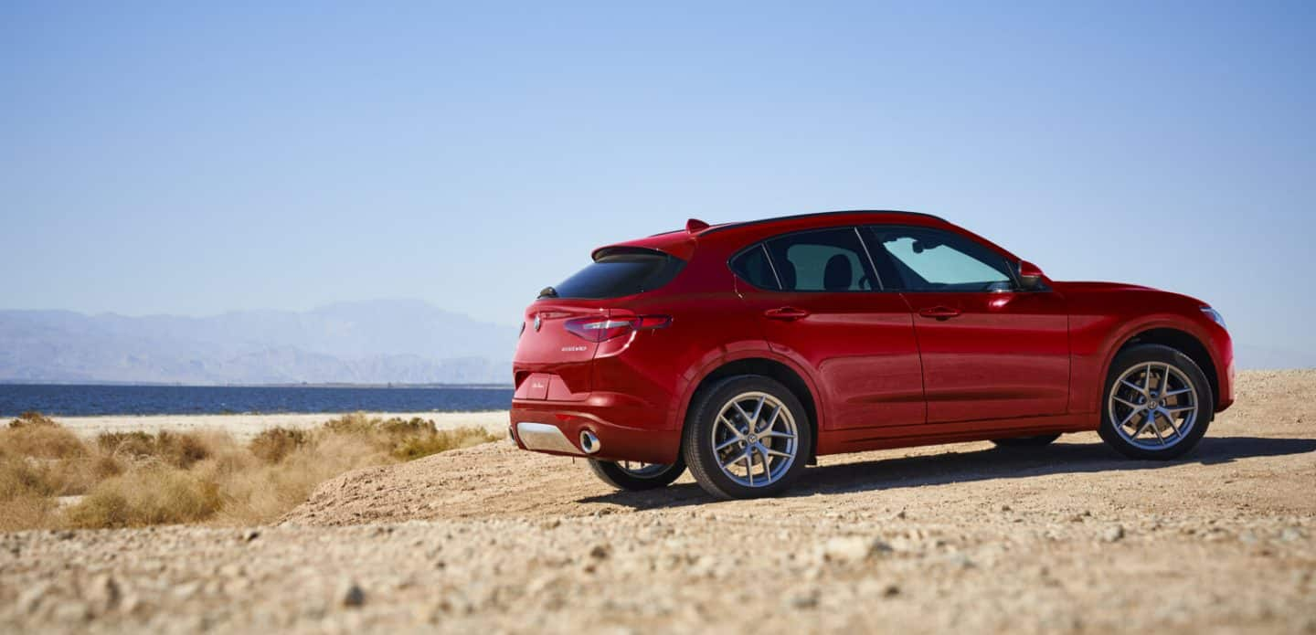 Display A three-quarter rear profile of the 2020 Alfa Romeo Stelvio parked at the beach.