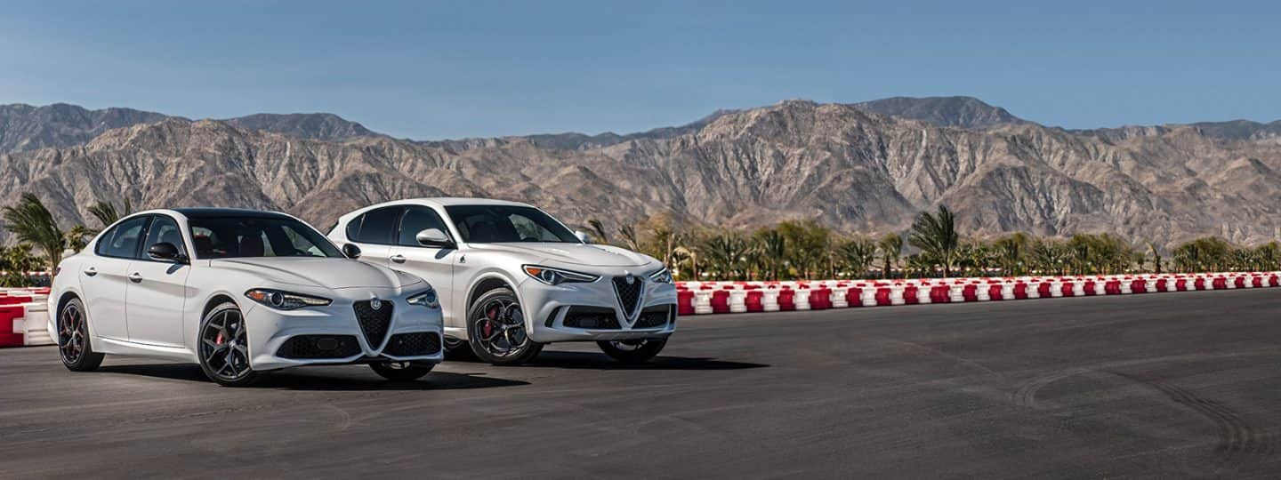 A 2020 Alfa Romeo Giulia Ti Sport and Alfa Romeo Stelvio Quadrifoglio parked side-by-side on a track near mountains.