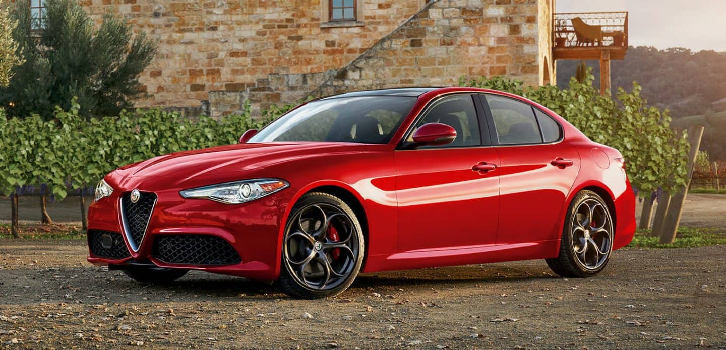 Display A three-quarter front view of the 2019 Alfa Romeo Giulia parked next to a buildiong in a rural area.